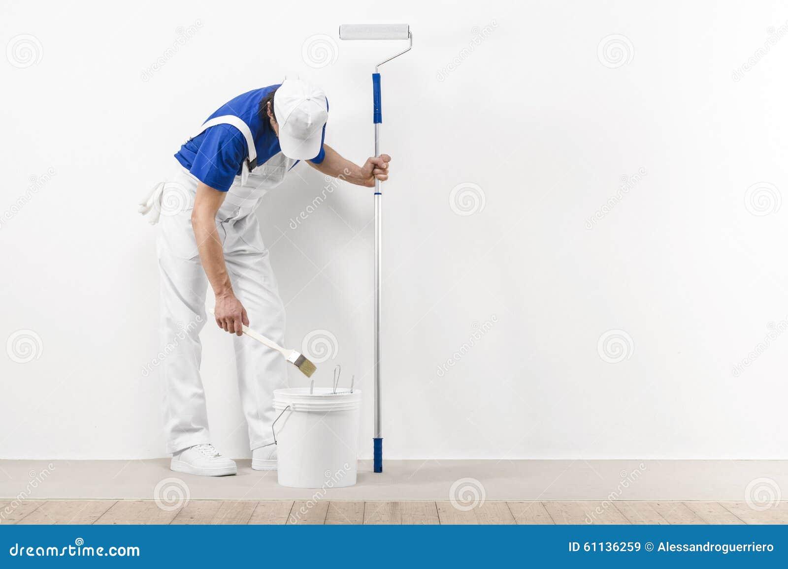 L uomo del pittore con paitroller prende il colore con il rullo della spazzola dalla t