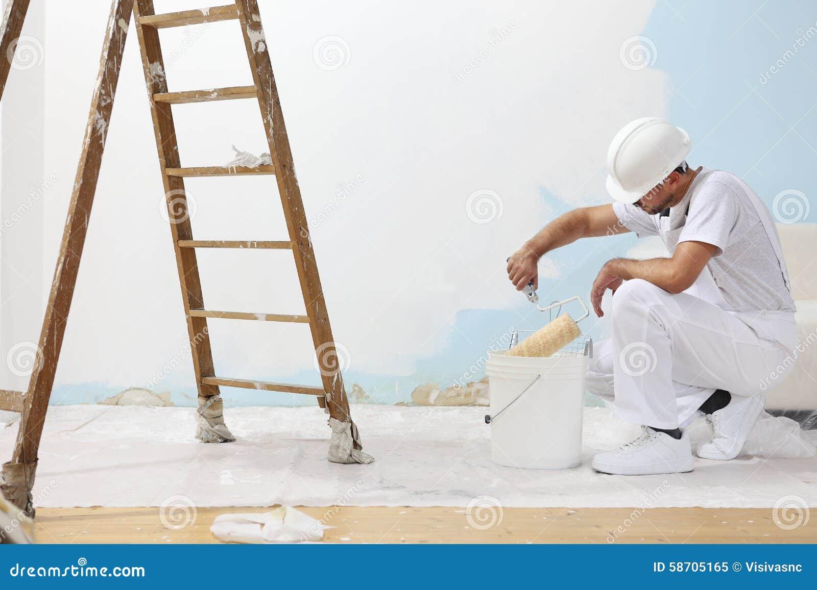 L uomo del pittore sul lavoro prende il colore con il rullo di pittura dalla b