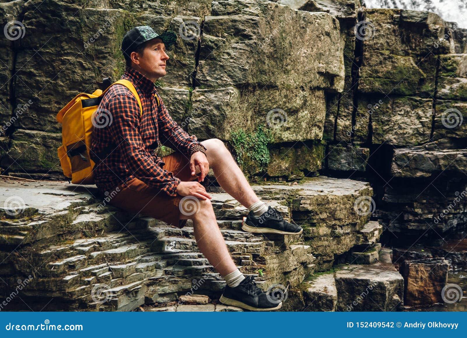 L uomo del viaggiatore con uno zaino si siede su una scogliera contro una cascata Spazio per il vostro messaggio di testo o conte