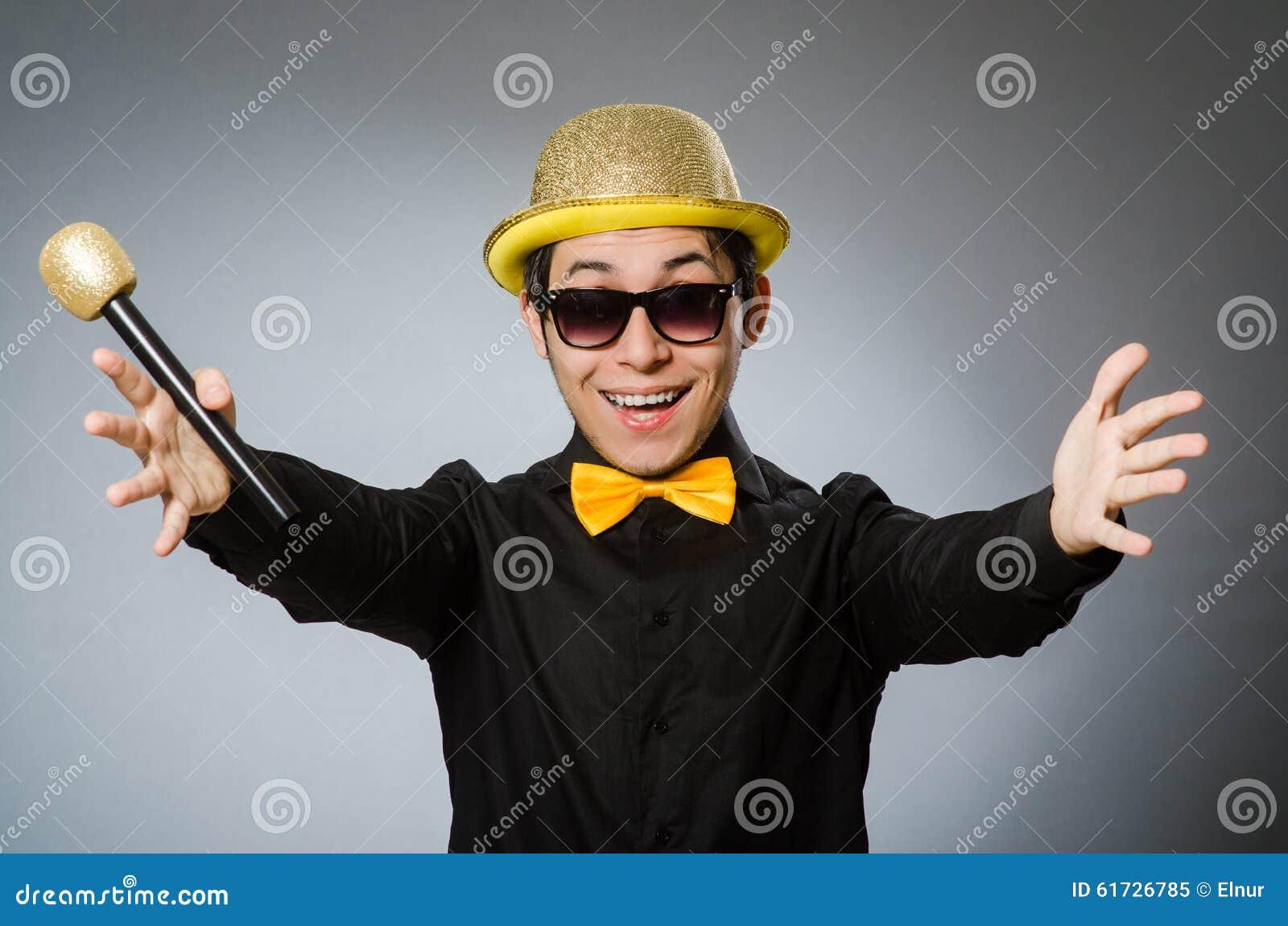 L uomo divertente con il mic nel concetto di karaoke