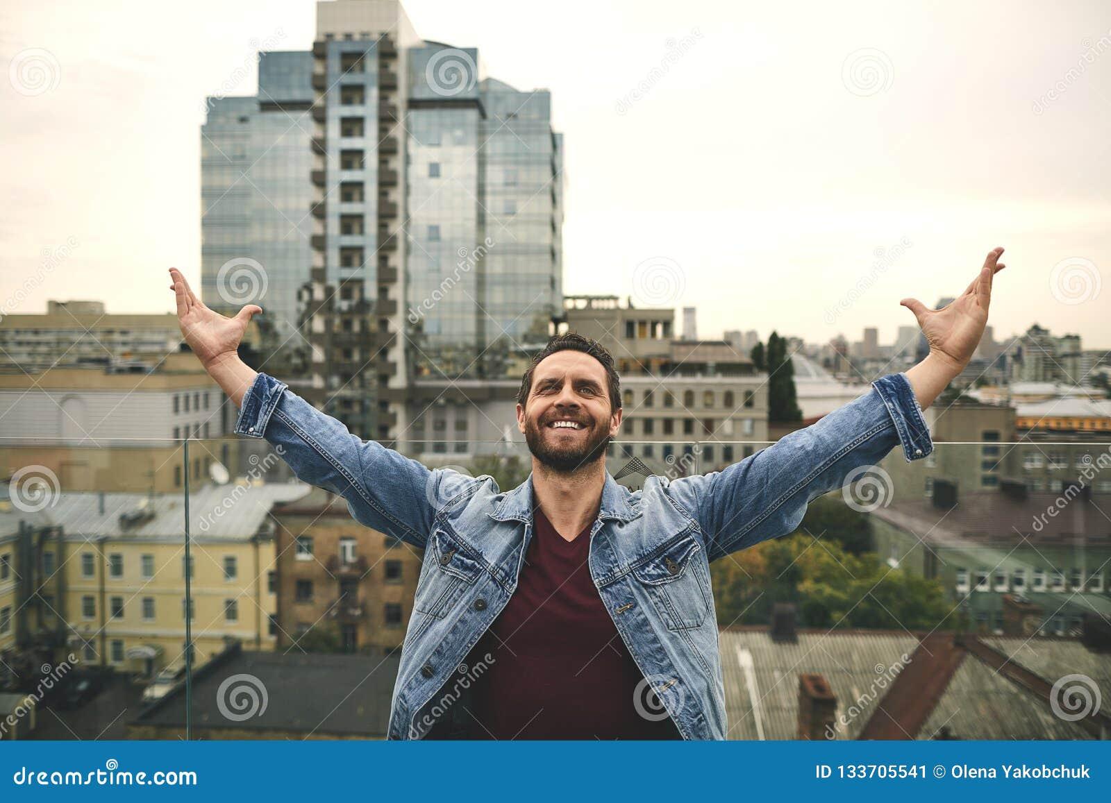 L uomo felice sta stando sul bello terrazzo