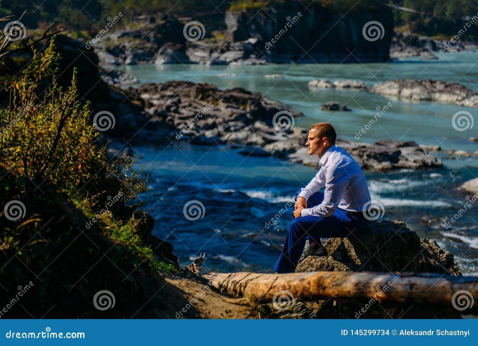 L uomo ha vestito i vestiti di affari che si siedono su una roccia dal fiume e dalle montagne