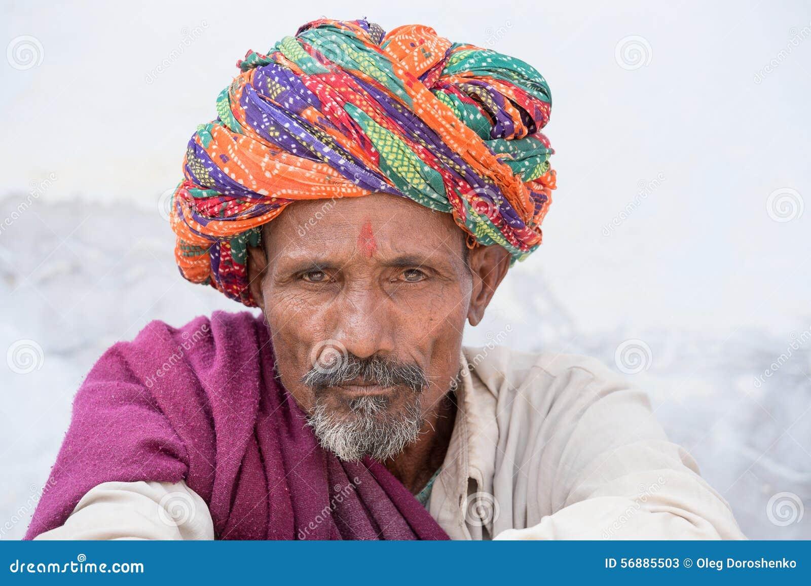 L uomo indiano, si siede sul ghat lungo il lago sacro Sarovar in Pushkar