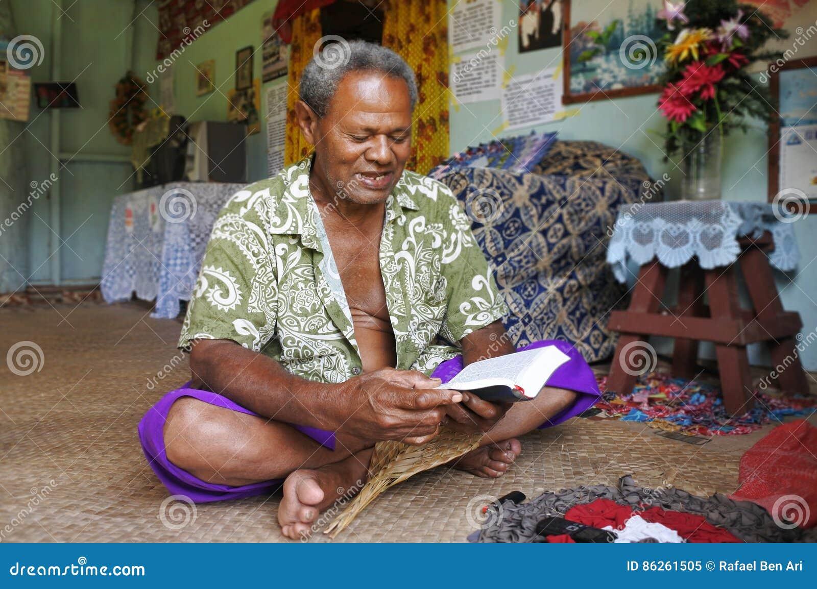 L uomo indigeno del Fijian legge la bibbia in Figi