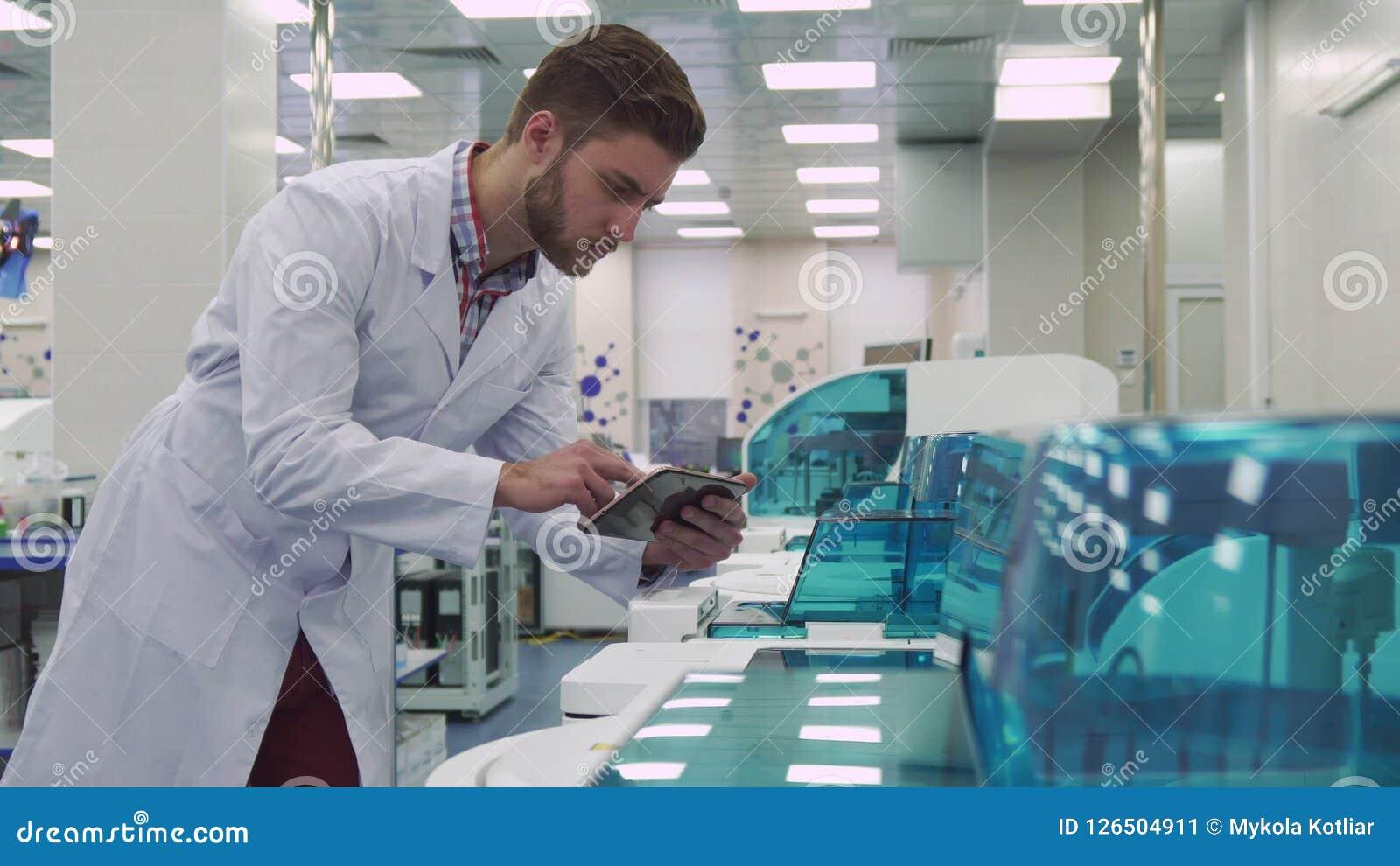 L uomo lancia sulla compressa vicino alla macchina del laboratorio