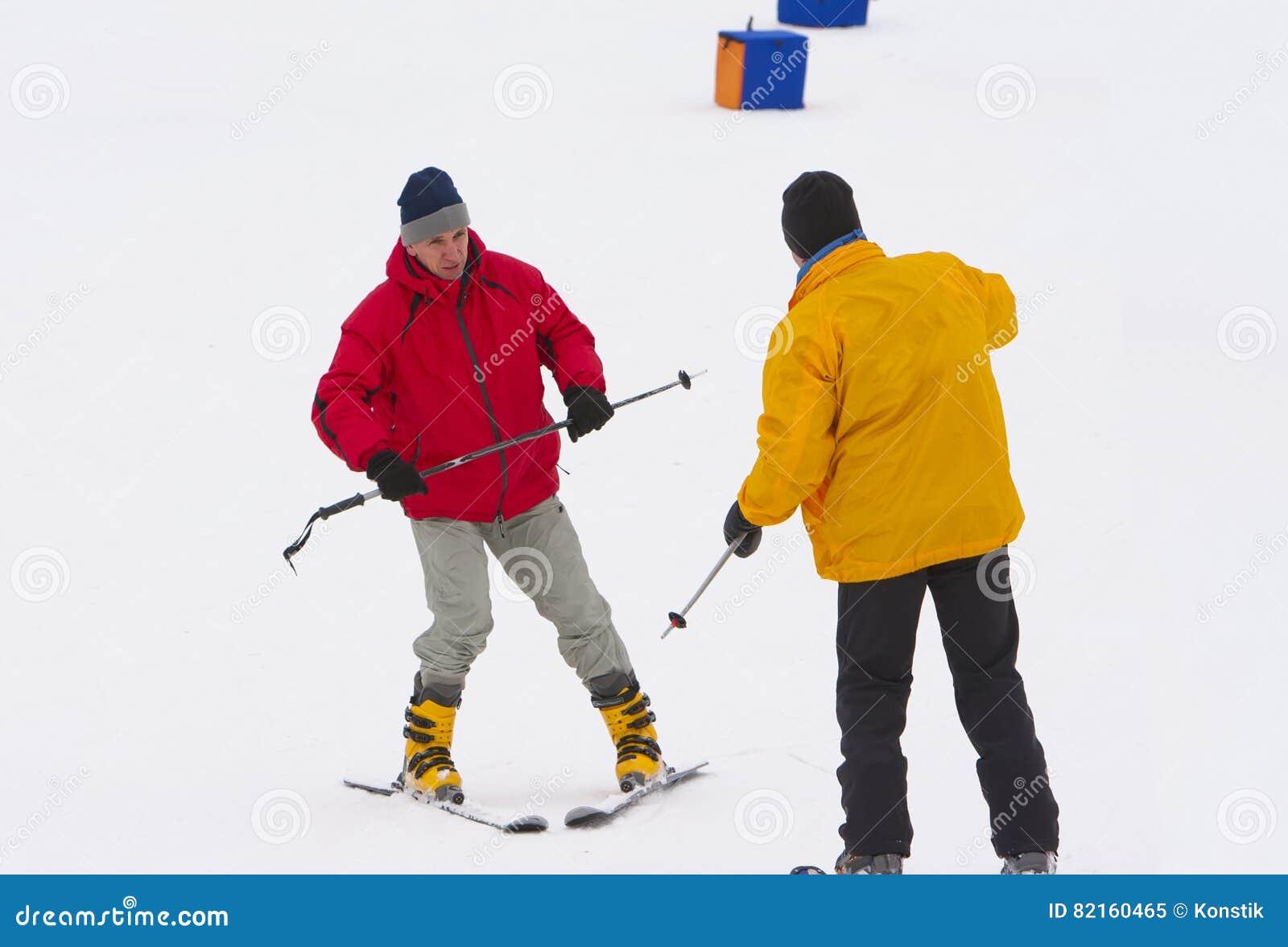 L uomo maturo impara guidare la corsa con gli sci della montagna