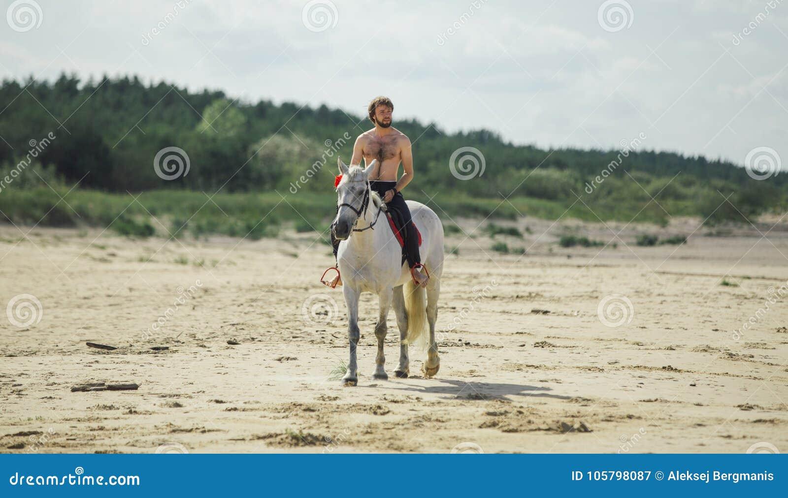 L uomo nacked sul cavallo bianco sulla spiaggia