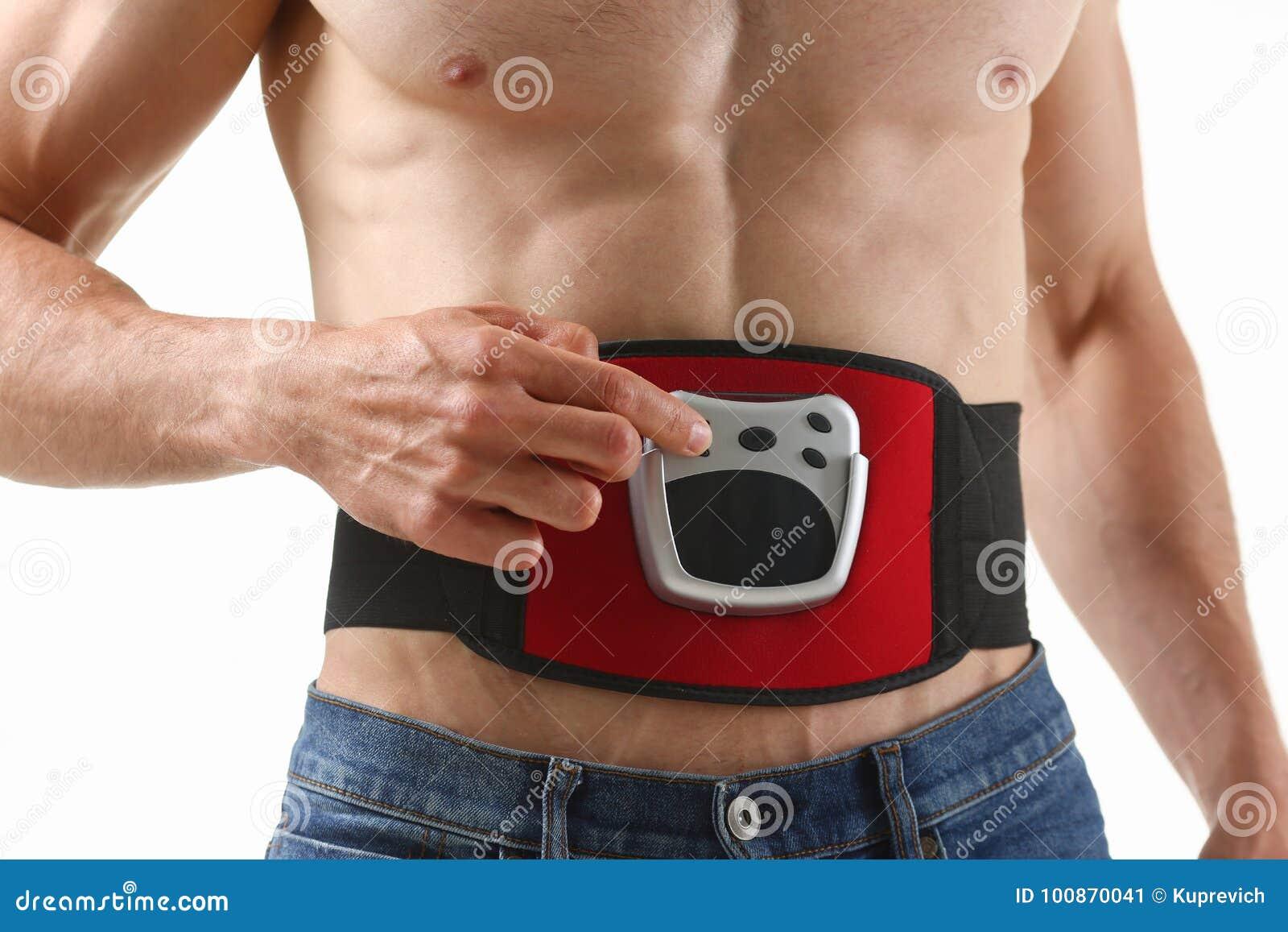 L uomo piegato atletico utilizza un simulatore elettrico della cinghia per la formazione della stampa