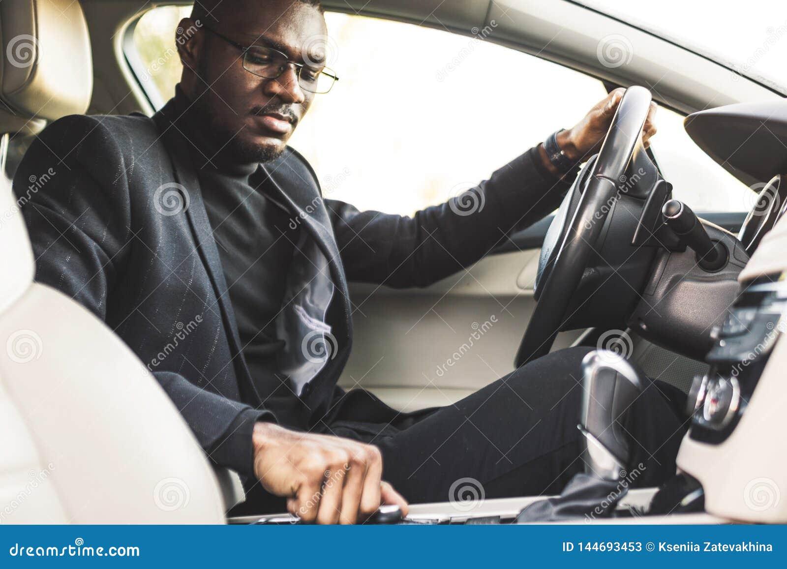 L uomo preme i bottoni nell automobile Adeguamento di audio controllo del volume