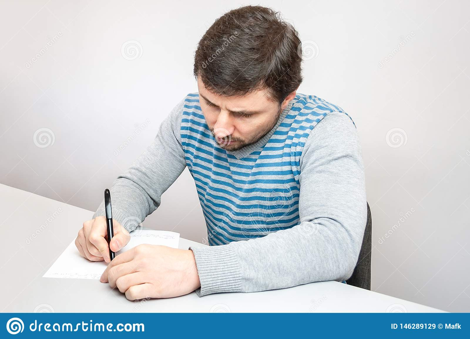L uomo premuroso bello in un maglione a strisce si siede alla tavola e scrive con una penna su carta