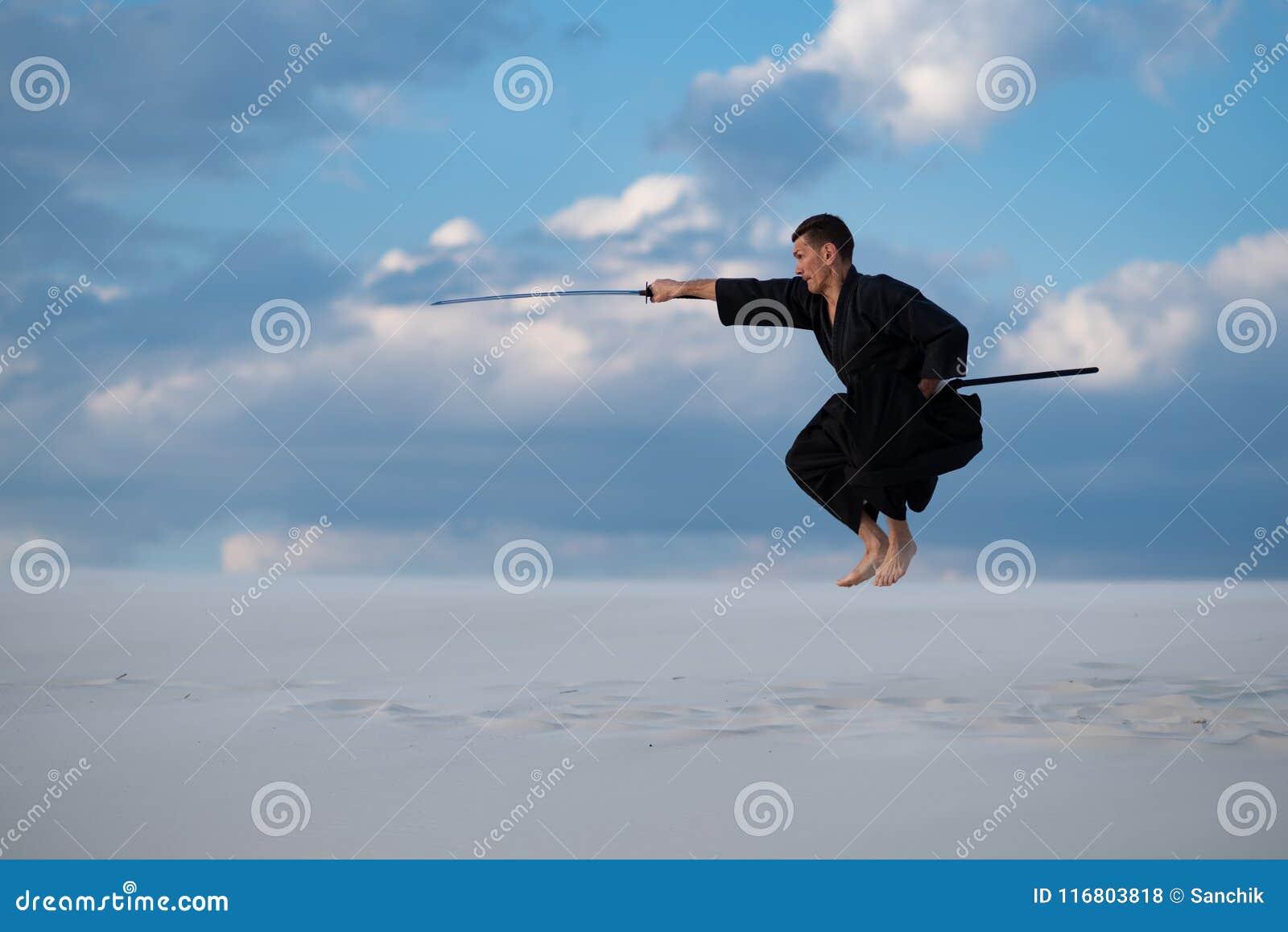 L uomo salta durante le arti marziali di addestramento in deserto
