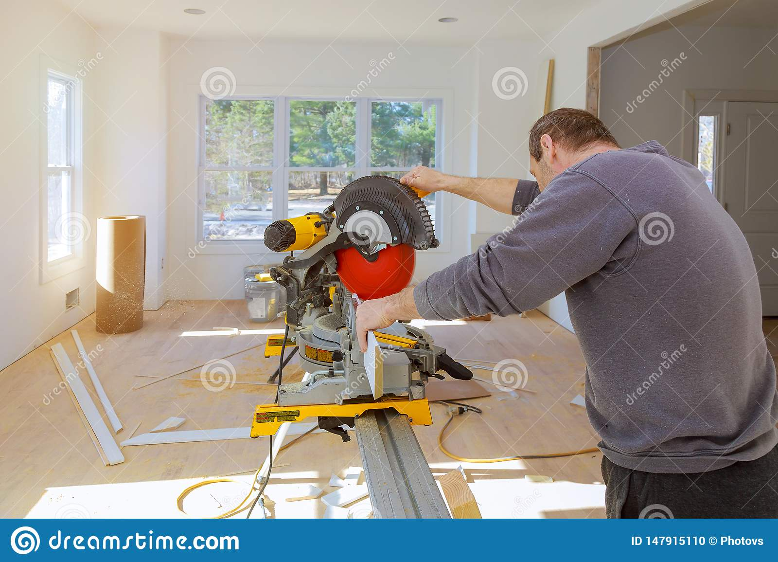 L uomo in seghe del costruttore del carpentiere di professione con sega circolare un modanatura basso della disposizione di legno