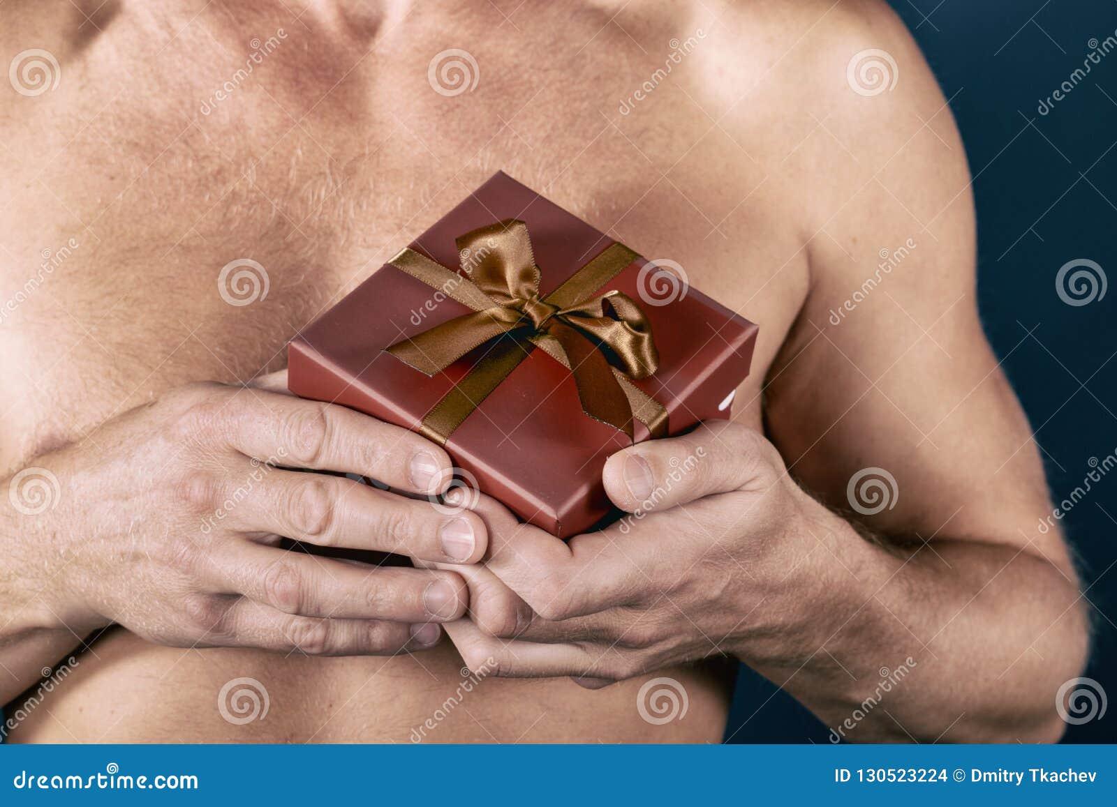 L uomo senza camicia giudica un contenitore di regalo isolato su bianco sorpresa Colpo dello studio Festa ed occasione speciale
