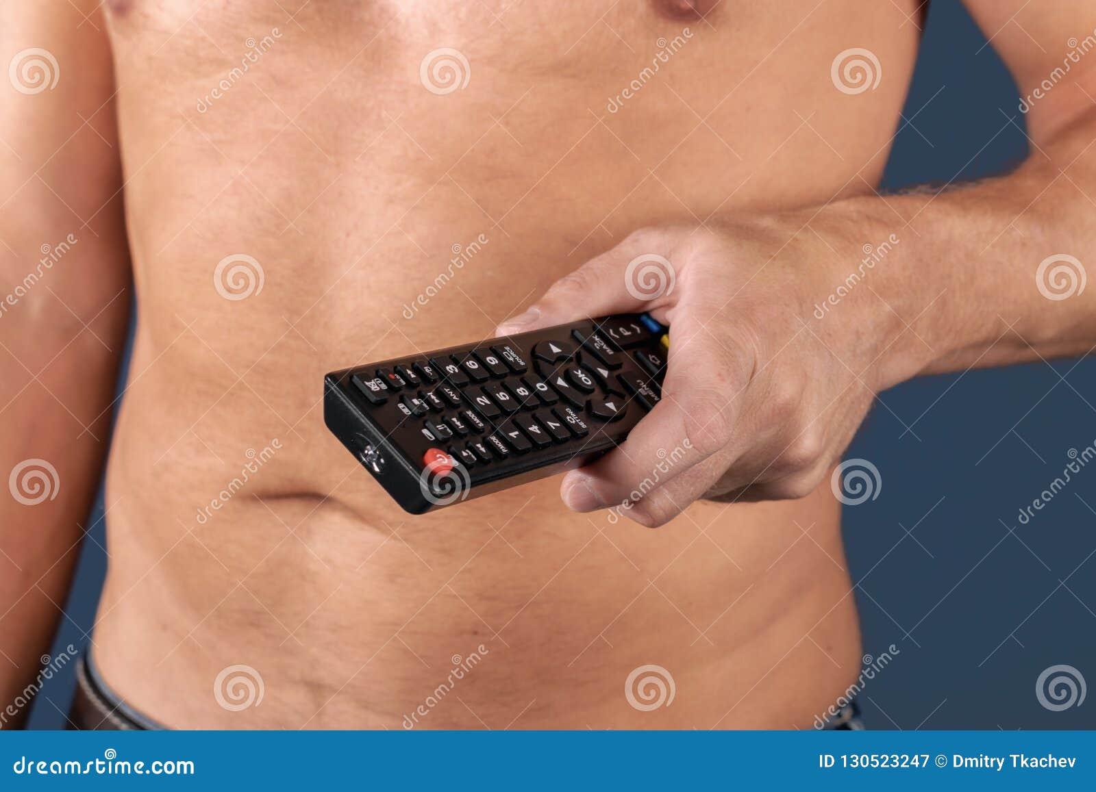L uomo senza camicia tiene il telecomando a disposizione, isolato sopra fondo blu