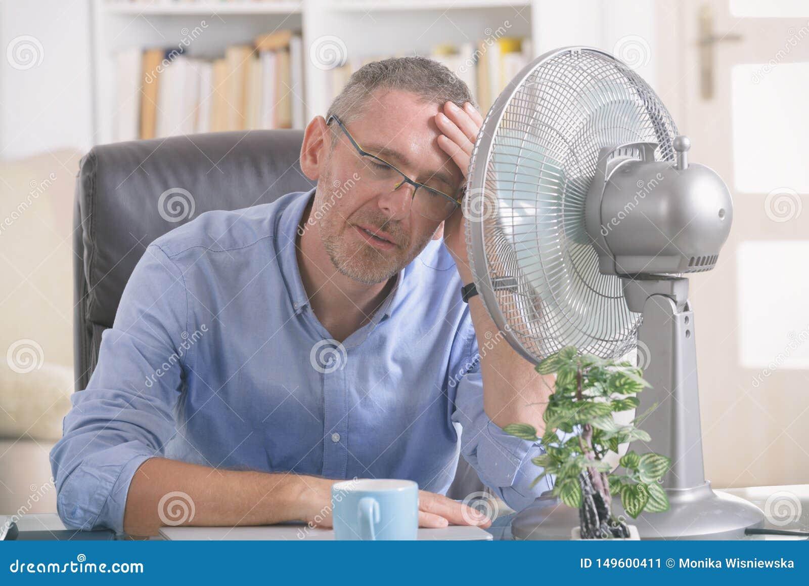 L uomo soffre dal calore nell ufficio o a casa