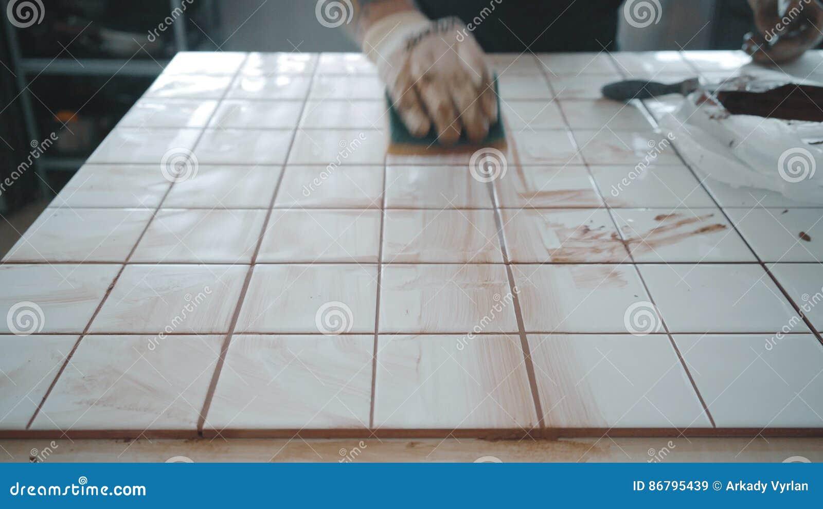 L uomo tatuato applica le piastrelle di ceramica sull insieme del