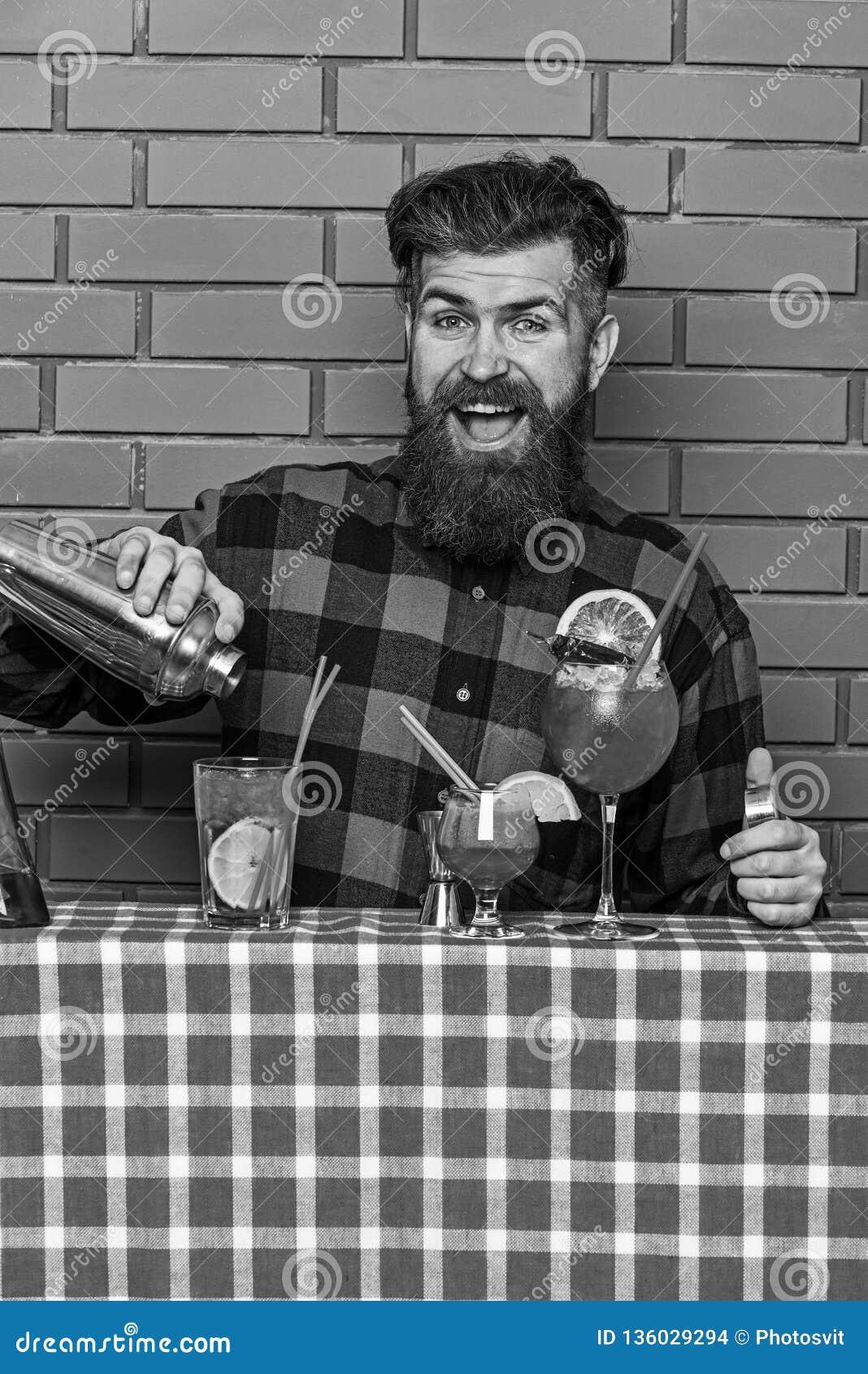 L uomo tiene l agitatore sul fondo del muro di mattoni Il barista con la barba ed il fronte felice fa il cocktail Il barista o i