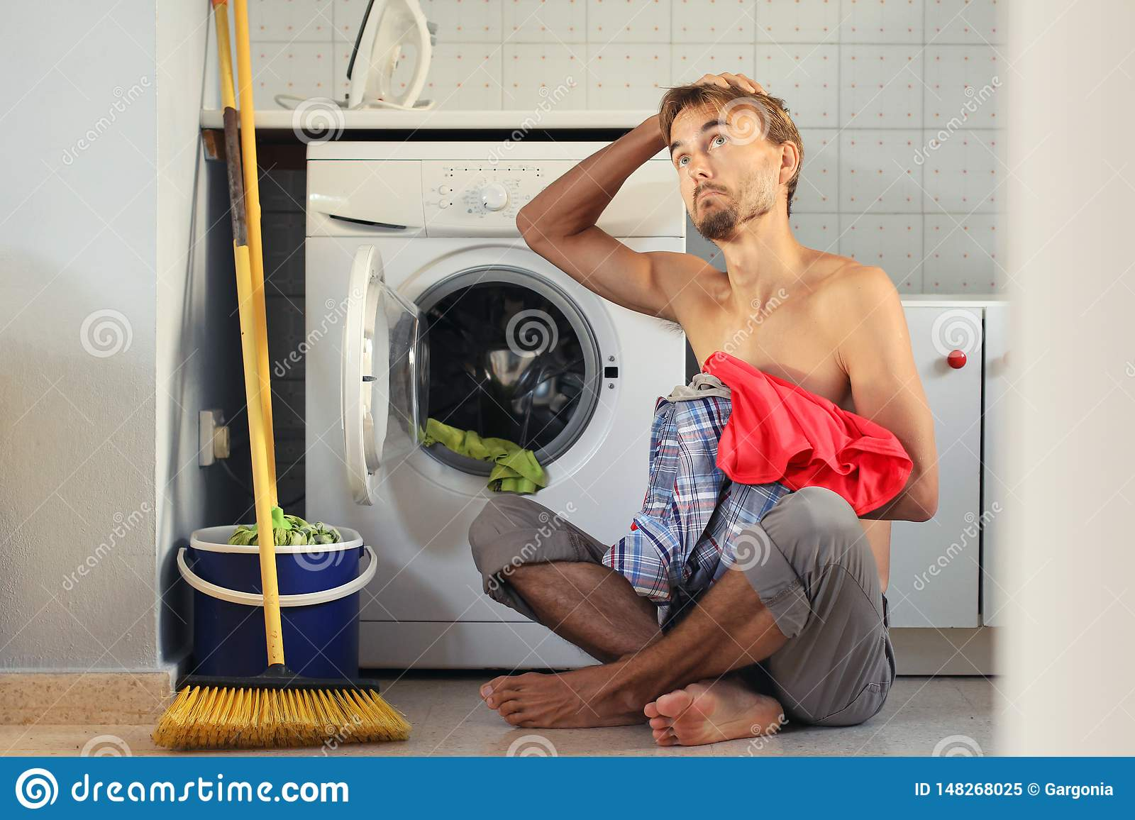 L uomo triste e imbarazzato di sguardo carica la lavanderia nella lavatrice Casalinga maschio, concetto del celibe