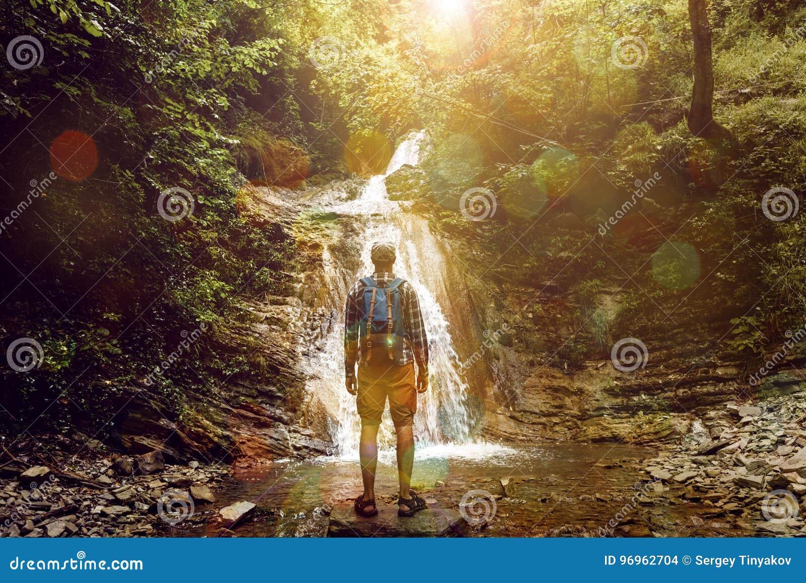 L uomo turistico ha raggiunto la destinazione e gode della vista della cascata, la retrovisione, concetto di avventura di proposi