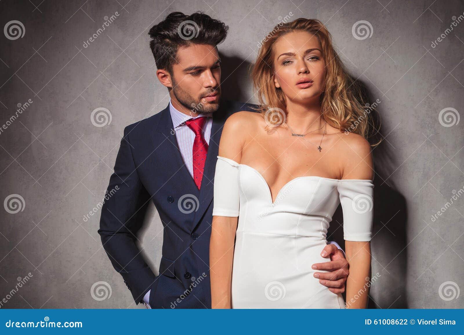 L uomo in vestito ed in legame esamina la sua donna bionda