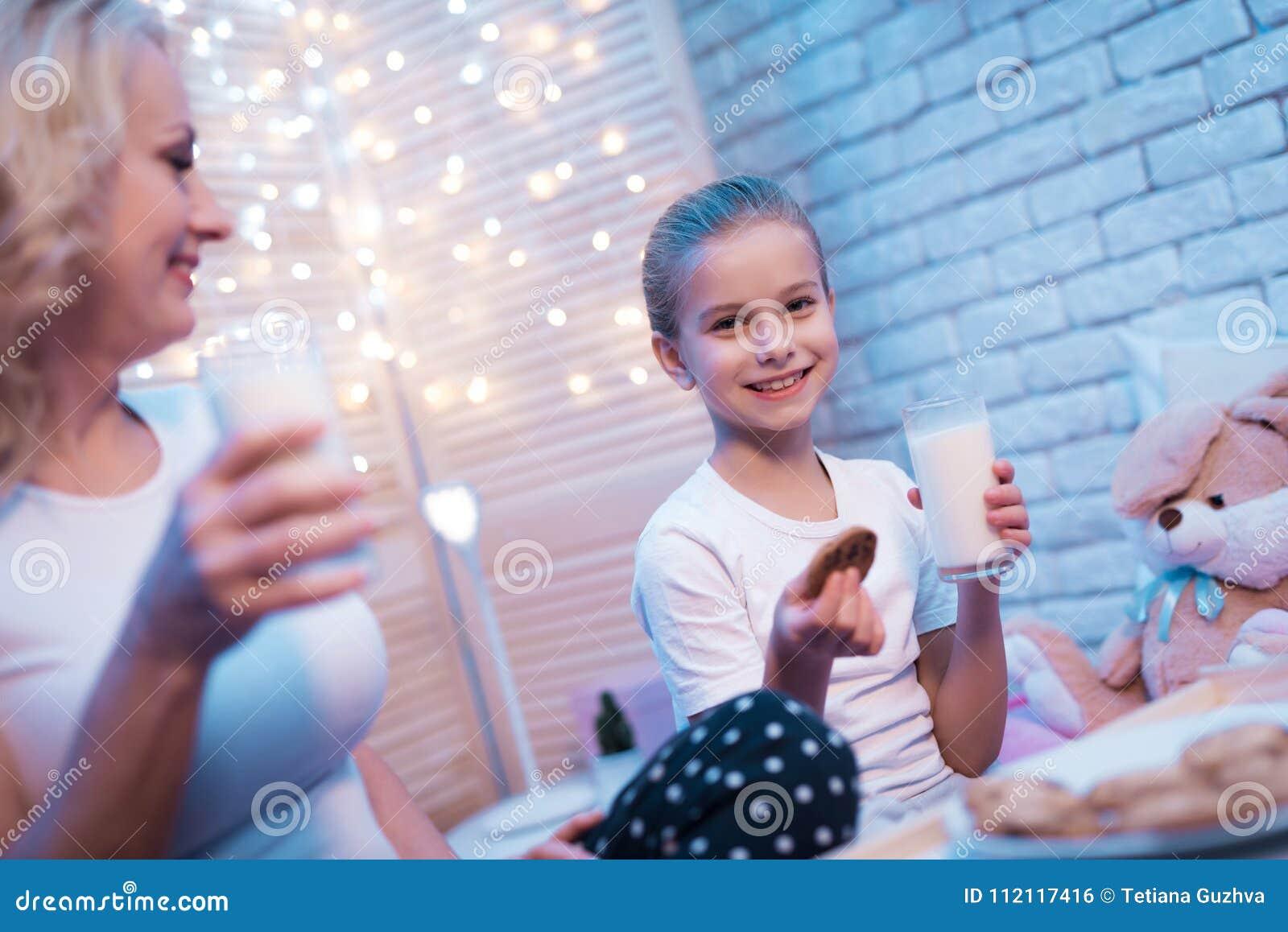 La abuela y la nieta están gozando de la leche y de las galletas en la noche en casa