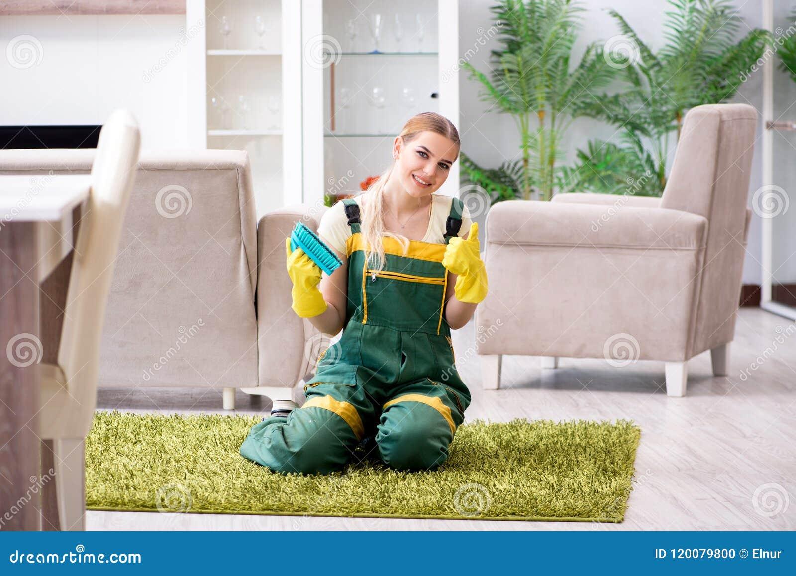 La alfombra femenina profesional de la limpieza del limpiador