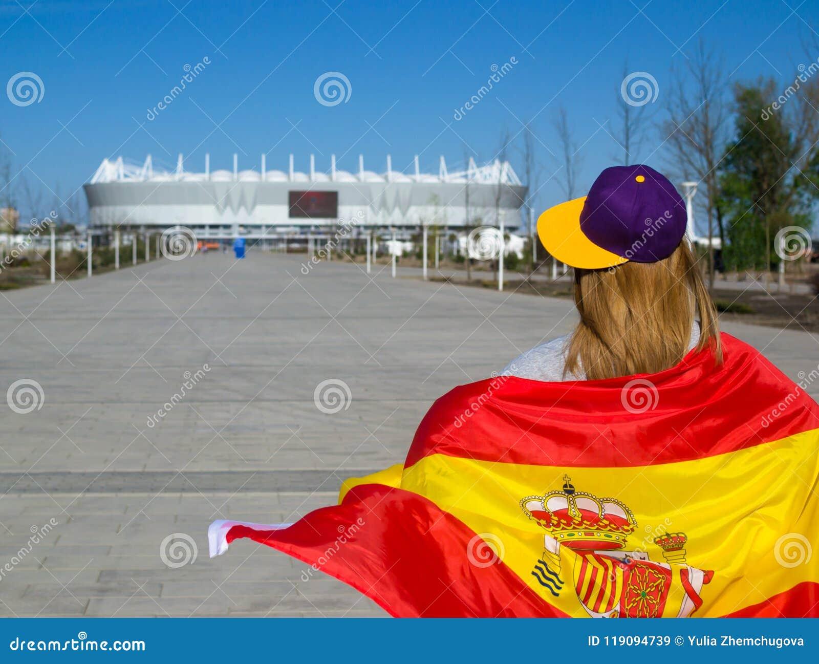 La animadora de la muchacha está dirigiendo al estadio de fútbol con la bandera española