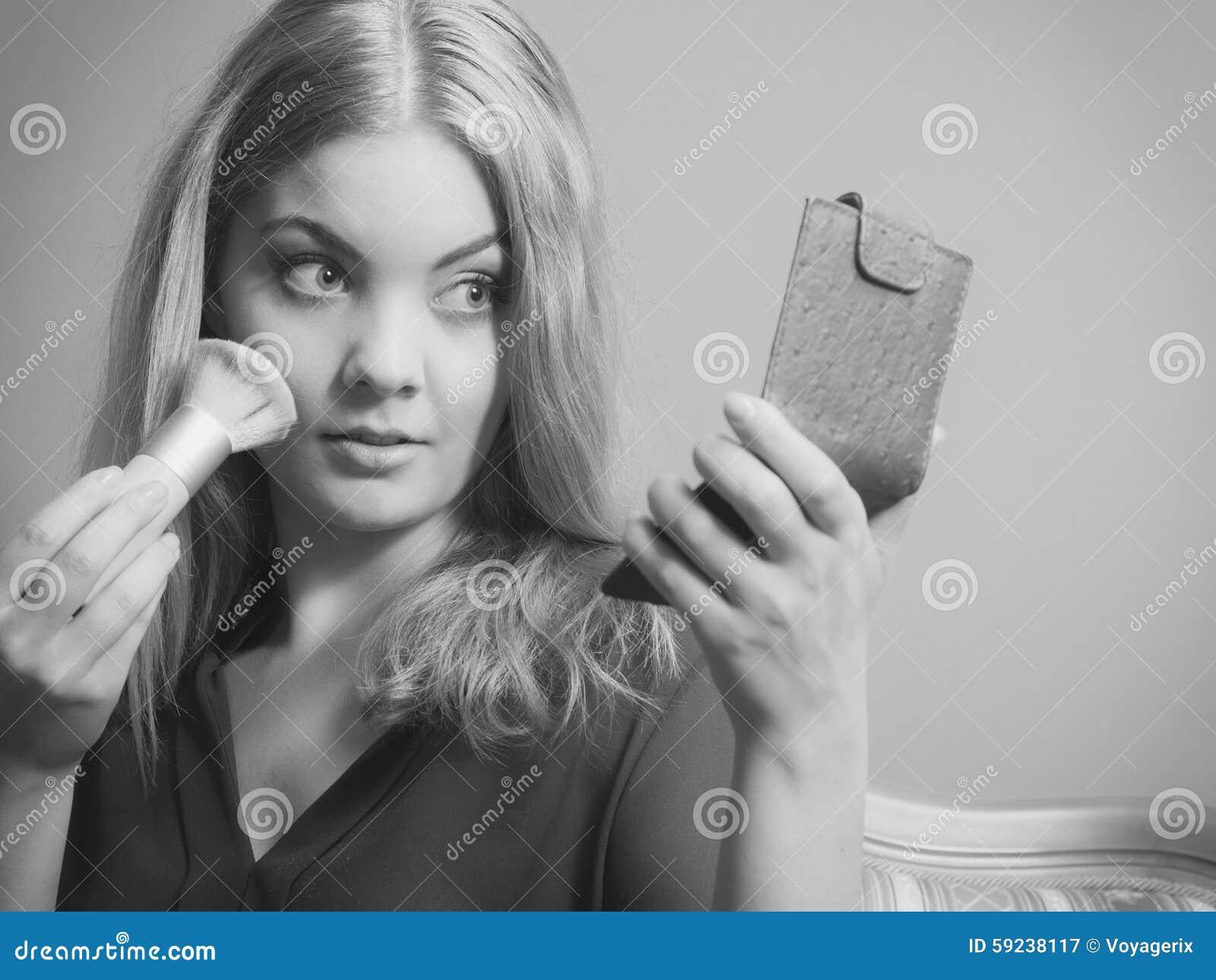 La aplicación atractiva de la mujer compone con el cepillo