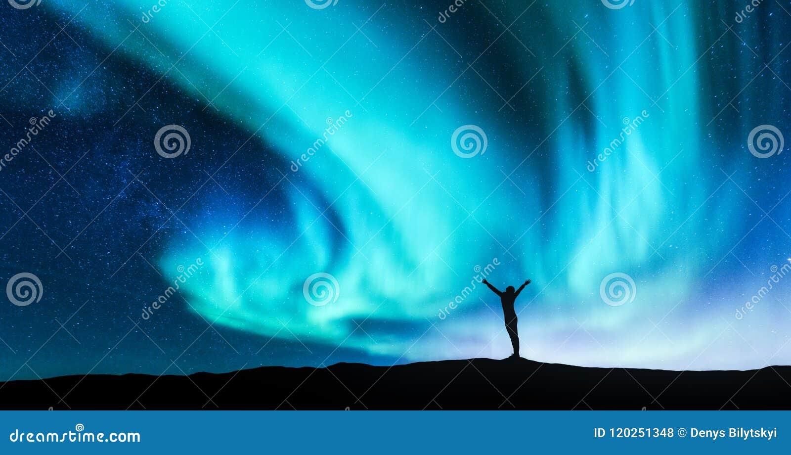 La aurora boreal y la silueta de una mujer con aumentado para arriba arma