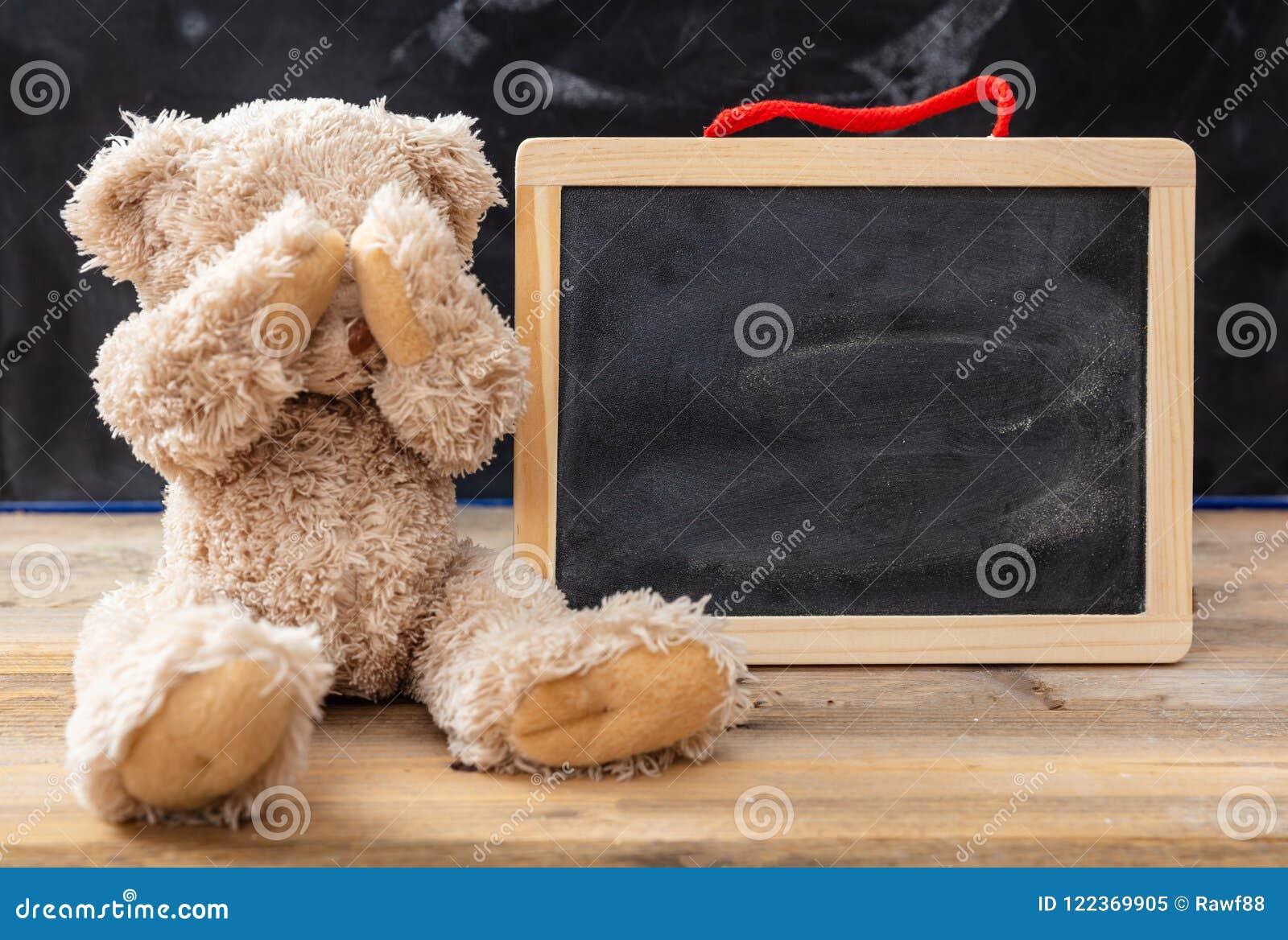 La bâche d ours de nounours observe et un tableau noir vide, l espace pour le texte