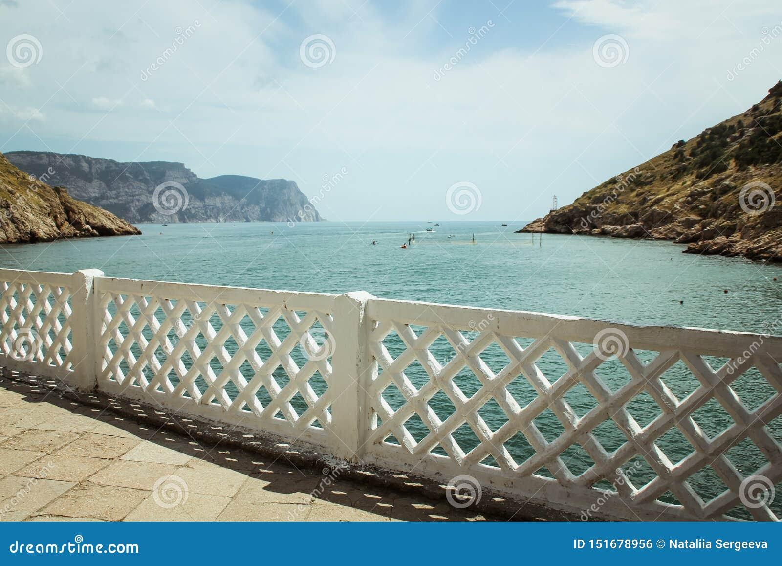 La bahía de Balaklava y las ruinas del arpicordio Genoese de la fortaleza Balaklava, Crimea La gente admira el mar