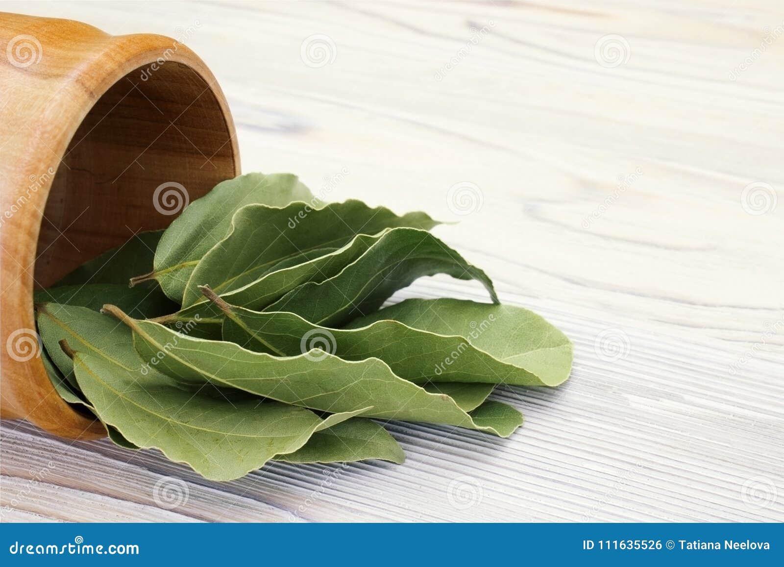 La baia aromatica secca lascia in una ciotola di legno sulla tavola rustica di legno bianca Foto del raccolto della baia dell all
