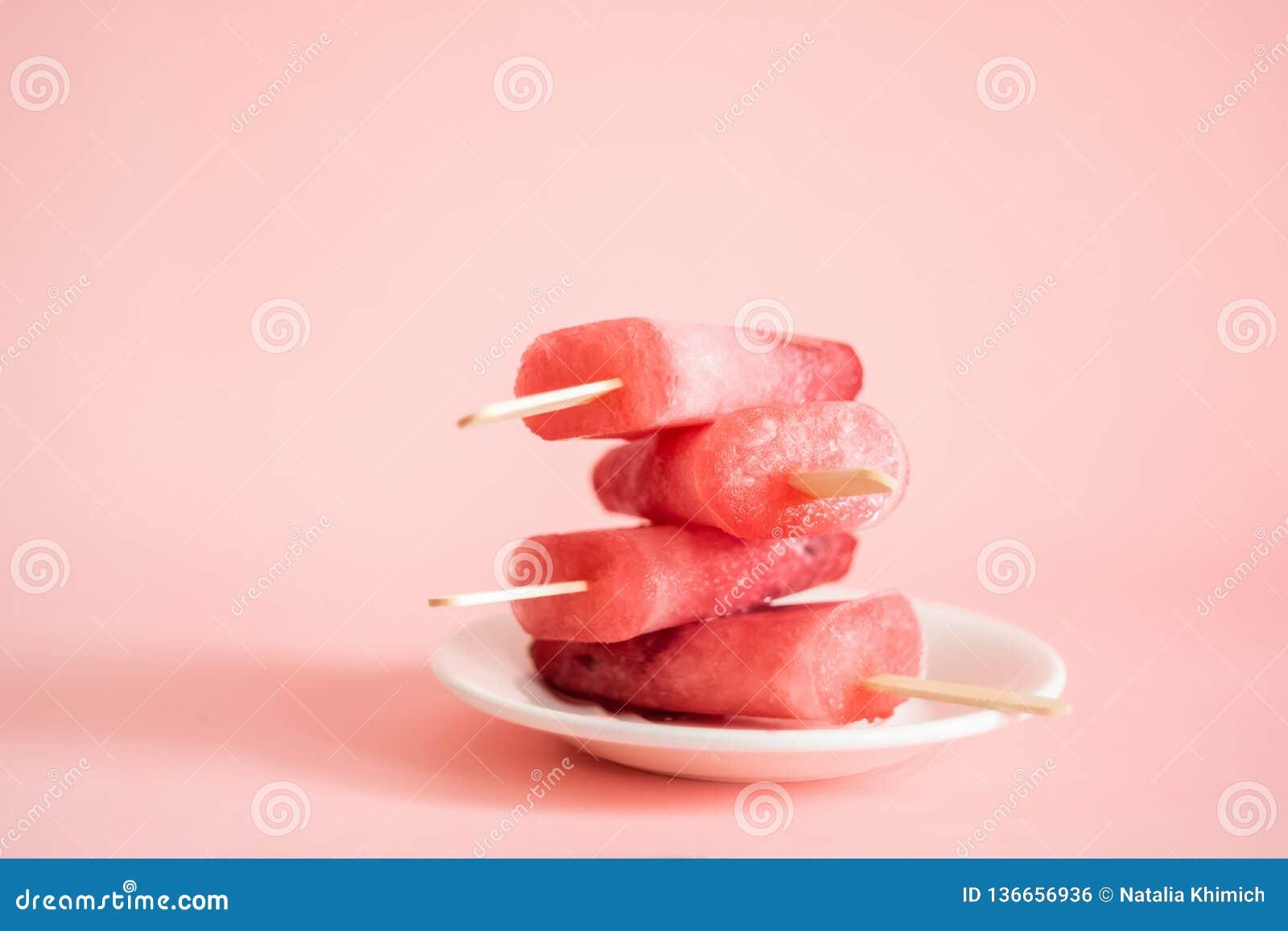 La baie ou les glaces à l eau a servi d un plat blanc Glace rose sur un fond rose Cadre horizontal de vue de face Copiez l espace