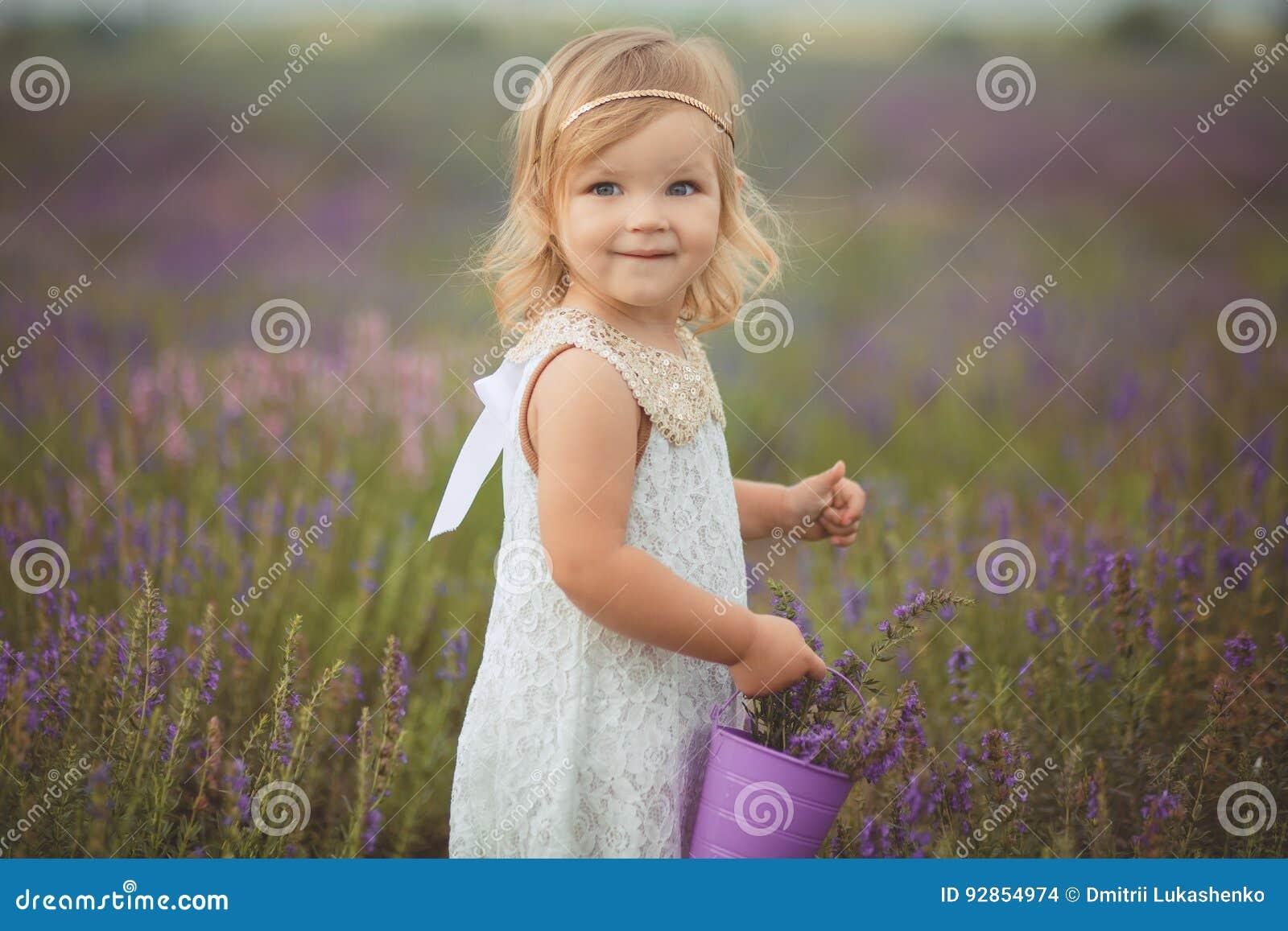 La bambina abbastanza sveglia sta portando il vestito bianco in un giacimento della lavanda che giudica un canestro pieno dei fio