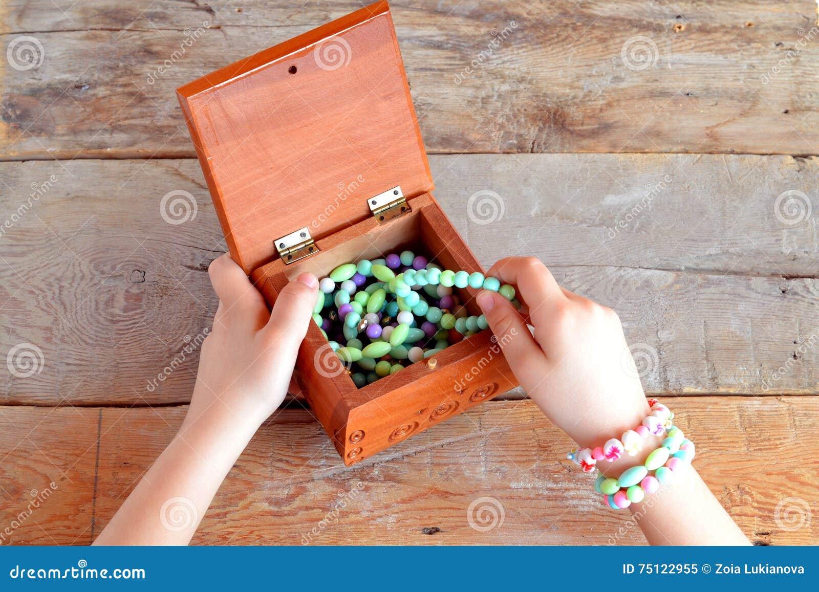 La bambina apre una scatola di braccialetti Vecchia priorità bassa di legno