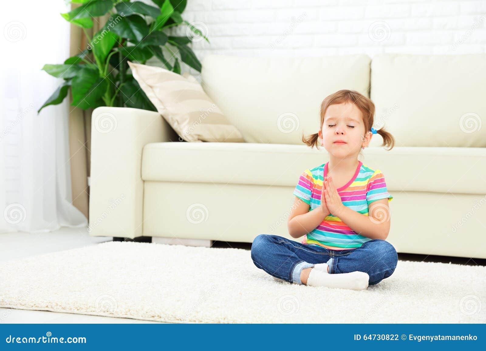 La bambina del bambino medita nella posizione di loto e pratica l yoga