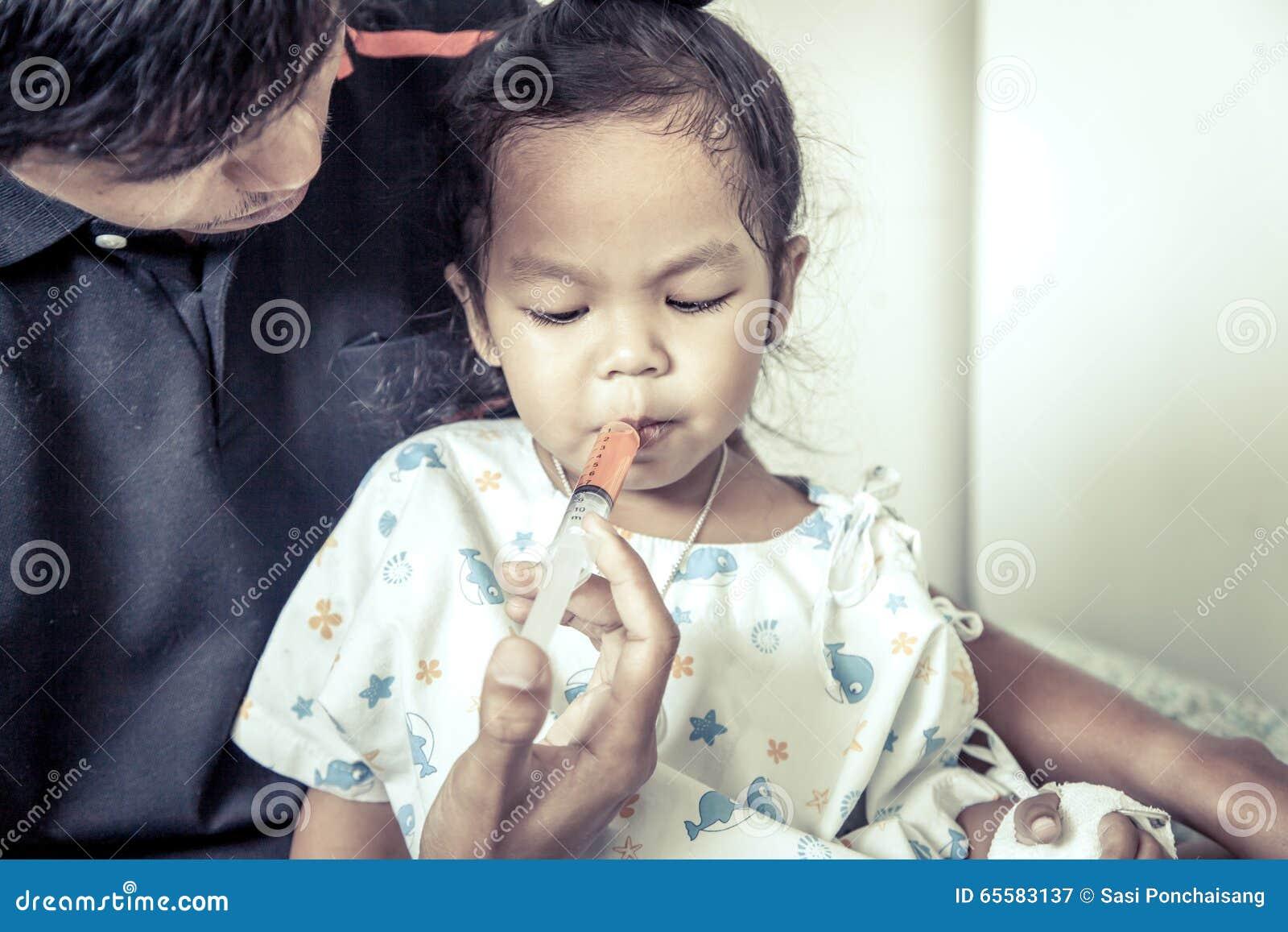 La bambina del bambino ottiene la medicina con una siringa nella sua bocca