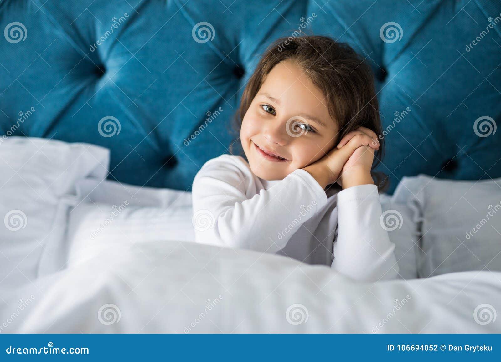 La bambina nella camera da letto sta sedendosi sul letto La bambina è durare pigiami Ragazza che si siede a letto