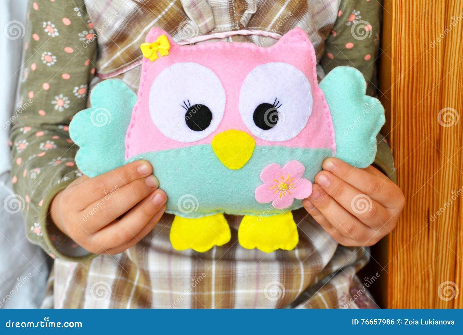 La bambina si siede e tiene un giocattolo del gufo nelle mani Giocattolo rosa e blu sveglio del feltro Decorazione del feltro del