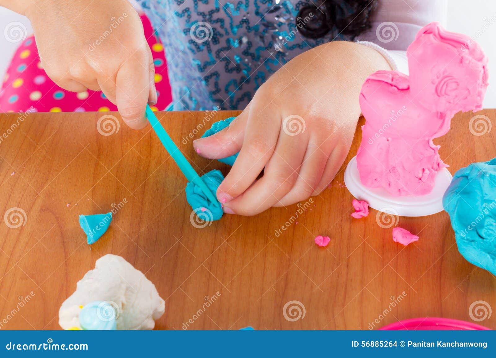 La bambina sta imparando usare la pasta variopinta del gioco