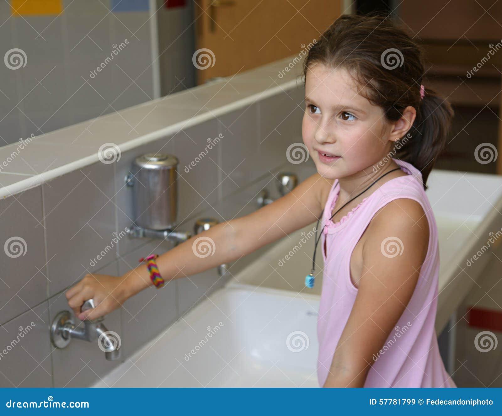 La Bambina Sta Lavando Le Sue Mani Nel Bagno Della Scuola Immagine ...