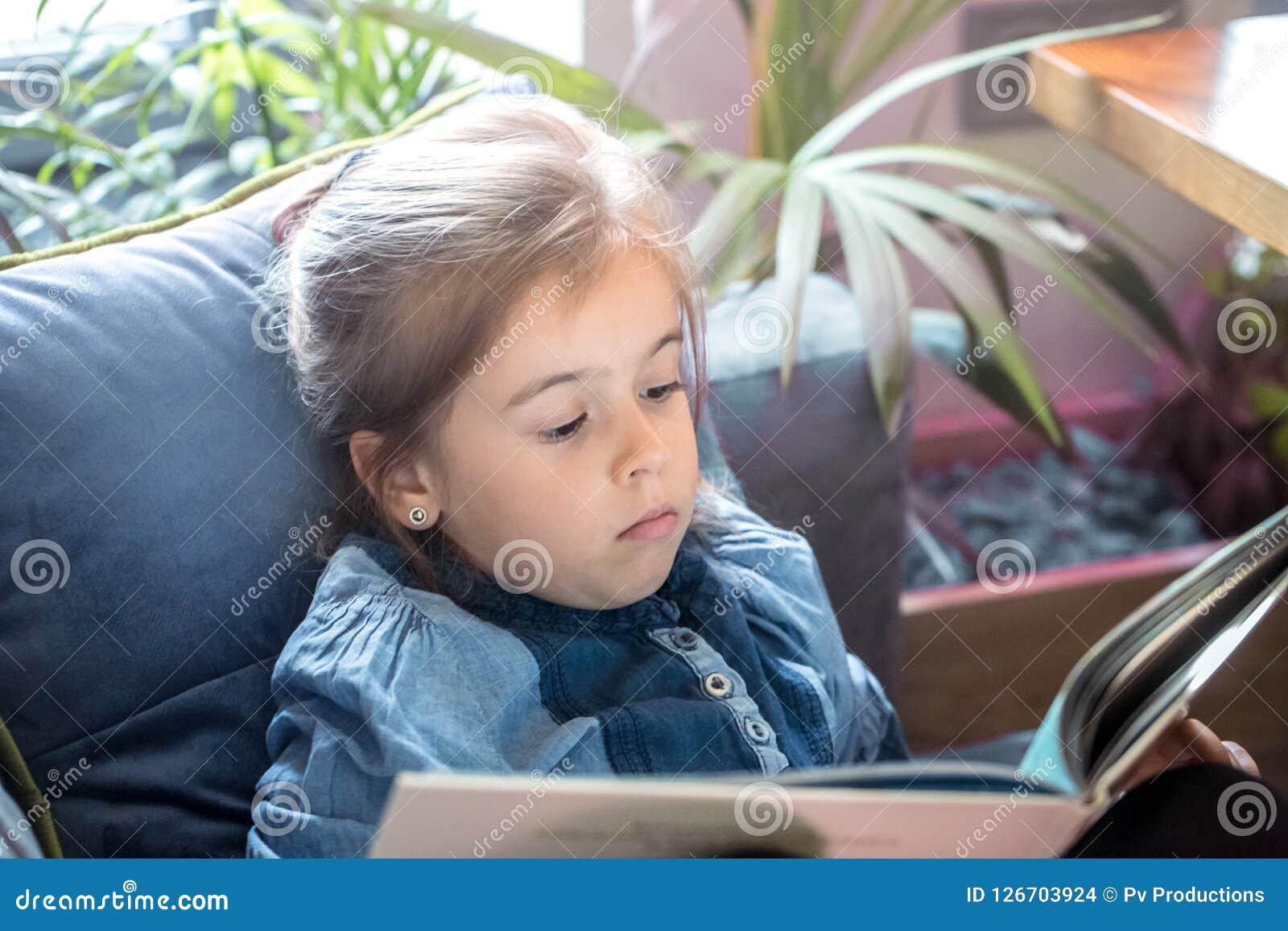 La bambina sta leggendo un libro nel salone sullo strato