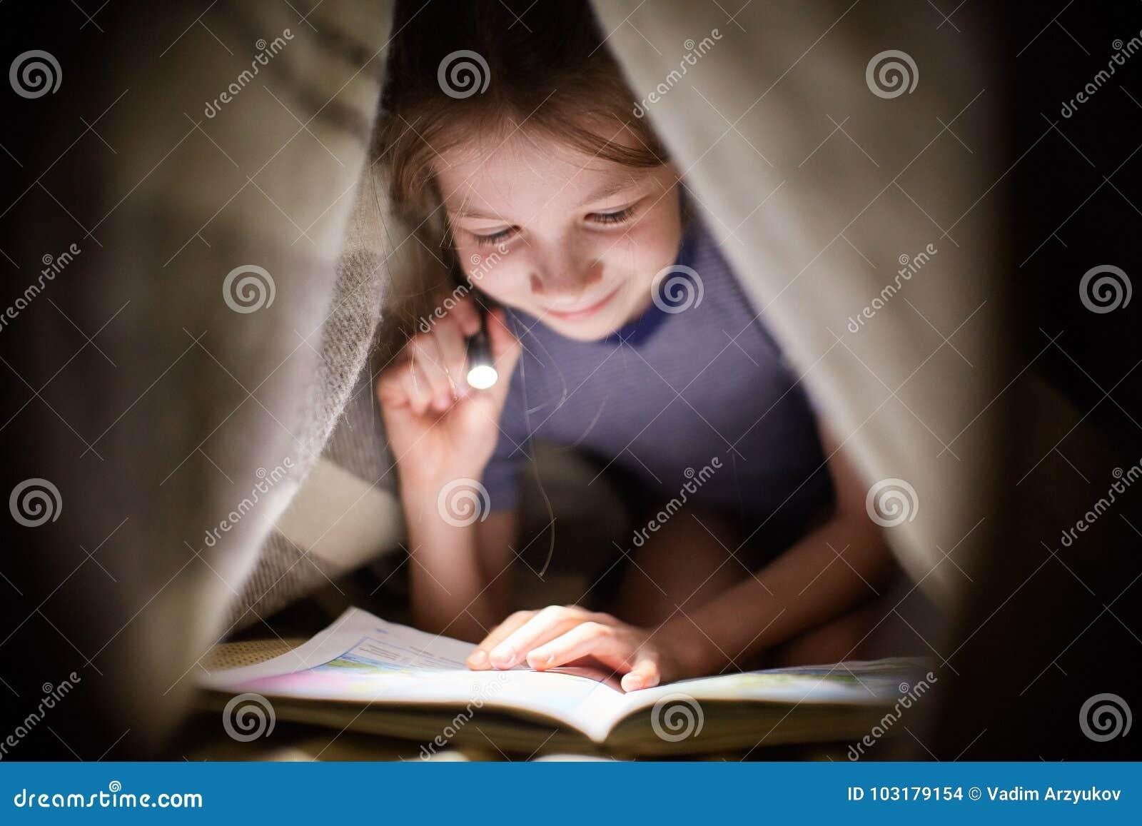 La bambina sta leggendo un libro sotto una coperta con una torcia elettrica in una stanza scura alla notte
