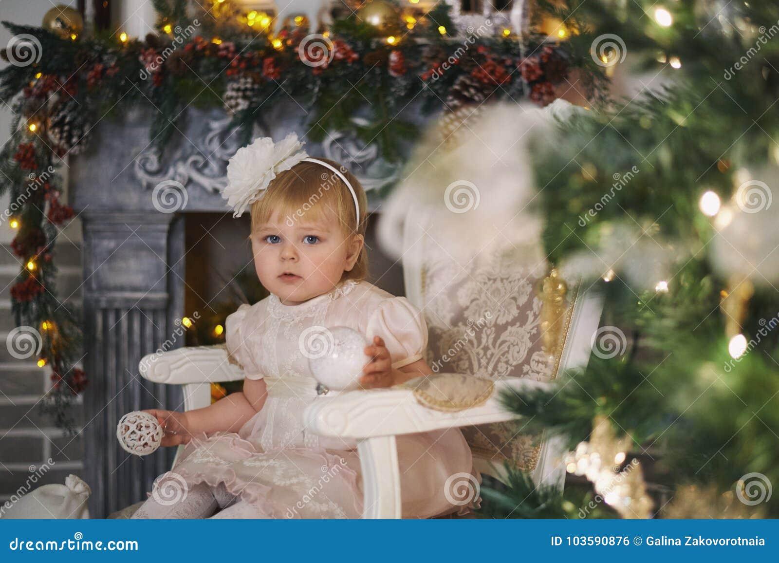 La bambina sta sedendosi su una sedia dall albero di Natale nell interno del ` s del nuovo anno