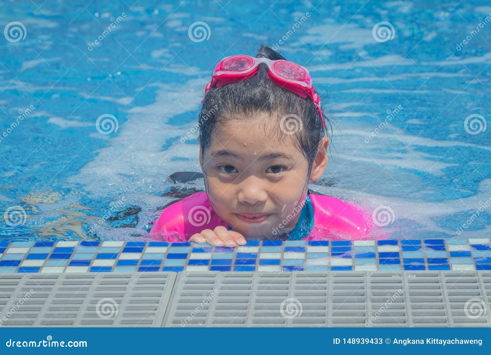 La bambina sveglia asiatica di felicità ha sensibilità divertente e gode di nella piscina