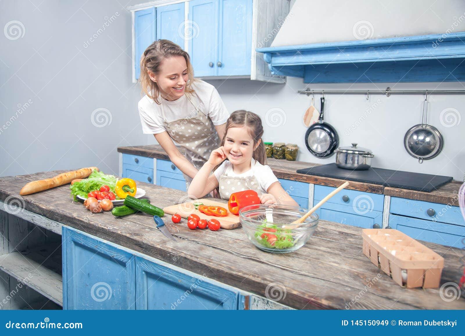 La bambina sveglia e la sua bella mamma in cappelli del ` s del cuoco unico stanno tagliando le verdure e stanno sorridendo mentr