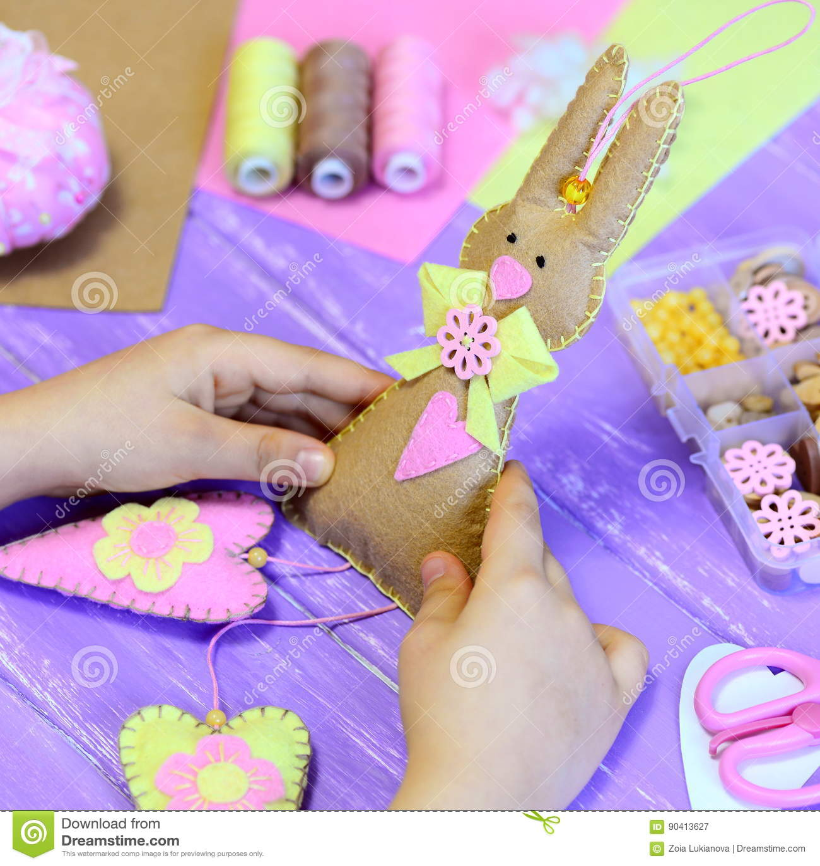 La bambina tiene un giocattolo del coniglietto di pasqua del feltro in mani La ragazza mostra un coniglietto del feltro con i cuo