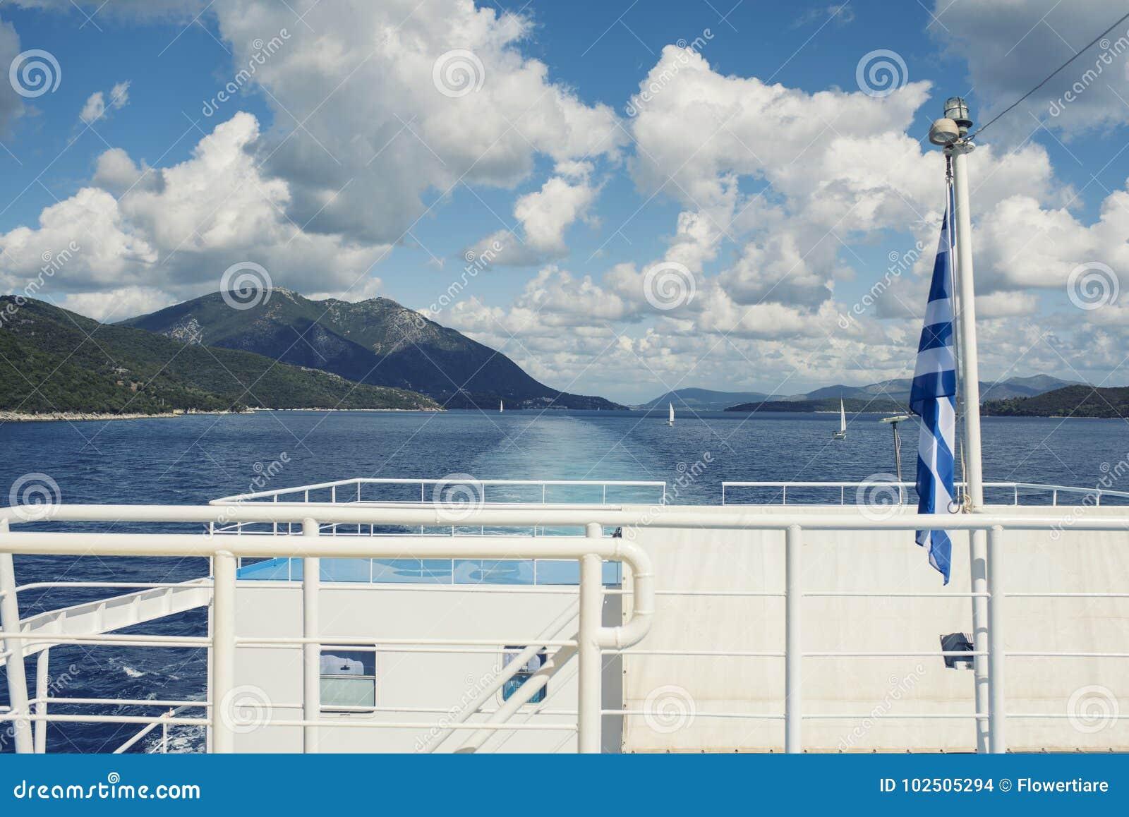 La bandiera greca sulla nave contro lo sfondo del mare delle isole Viaggio del mare nel mare ionico