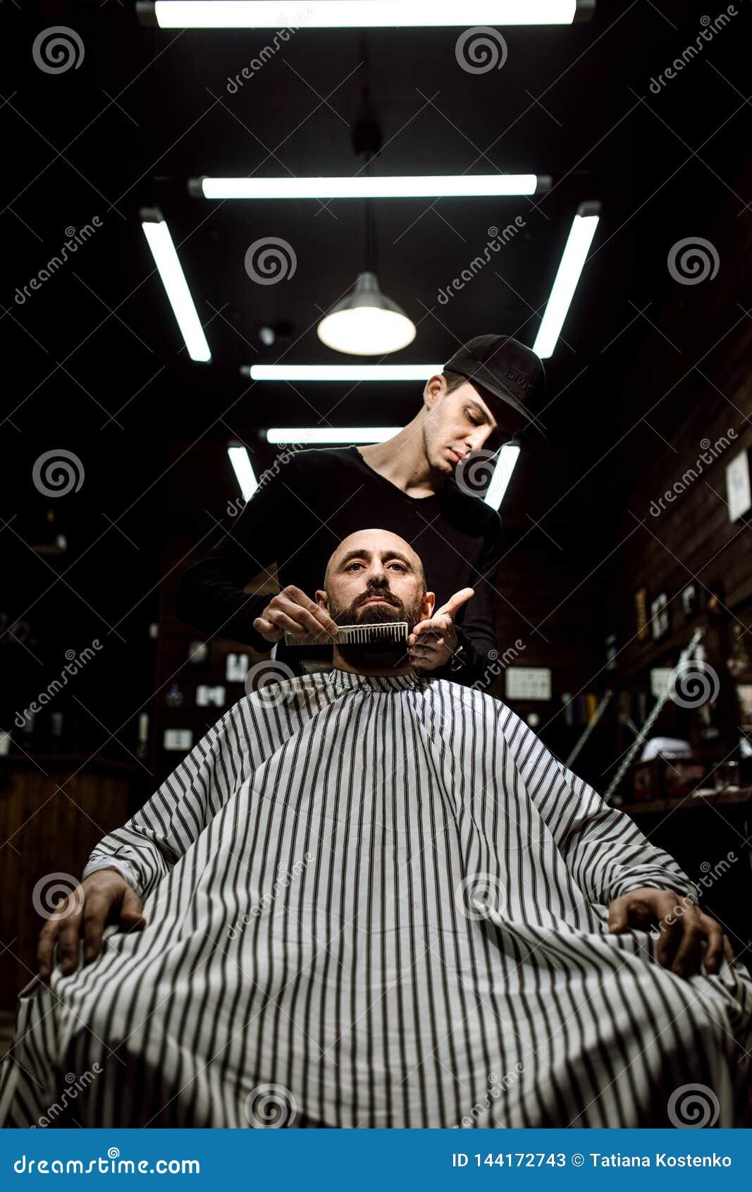 La barbería elegante El peluquero de la moda ordena la barba del hombre brutal que se sienta en la butaca