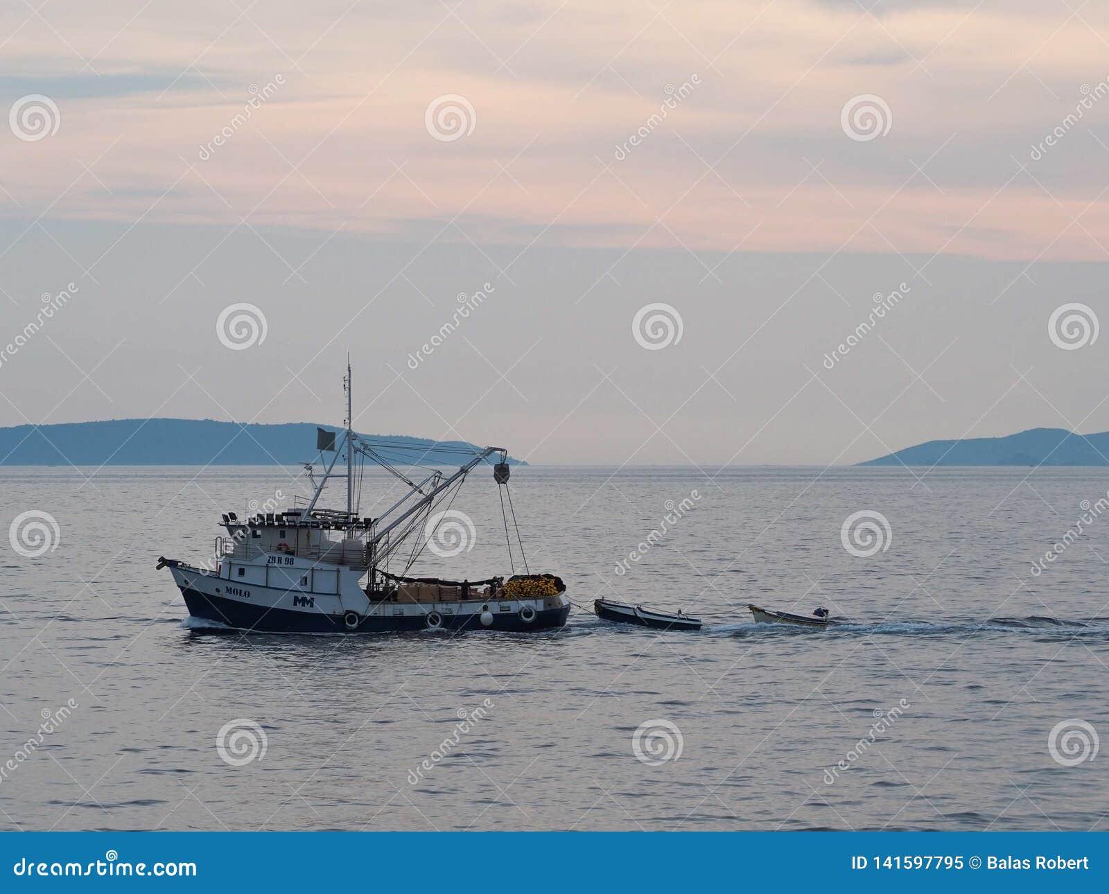 La barca tira due più piccole barche in mare
